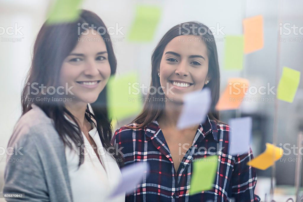 Smiling businesswoman with adhesive notes stuck on glass stock photo