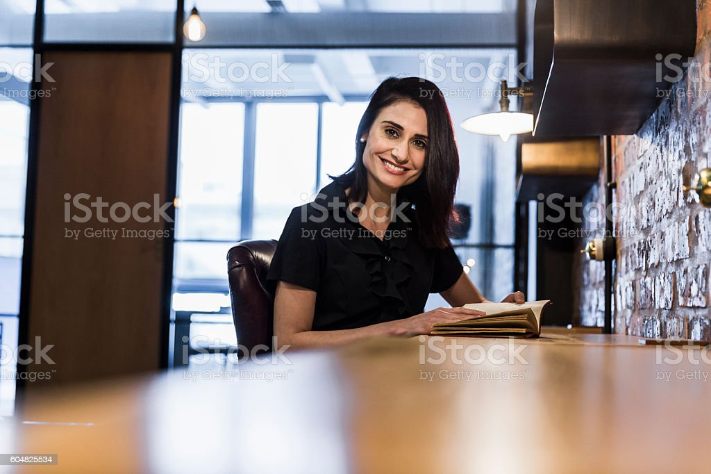 Smiling businesswoman with book at desk stock photo