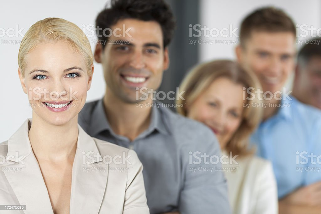 Smiling businesswoman with colleagues in background royalty-free stock photo