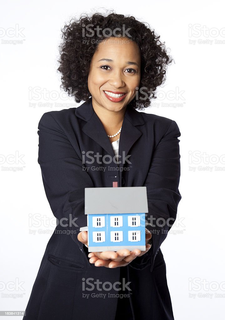 smiling businesswoman with miniature house royalty-free stock photo