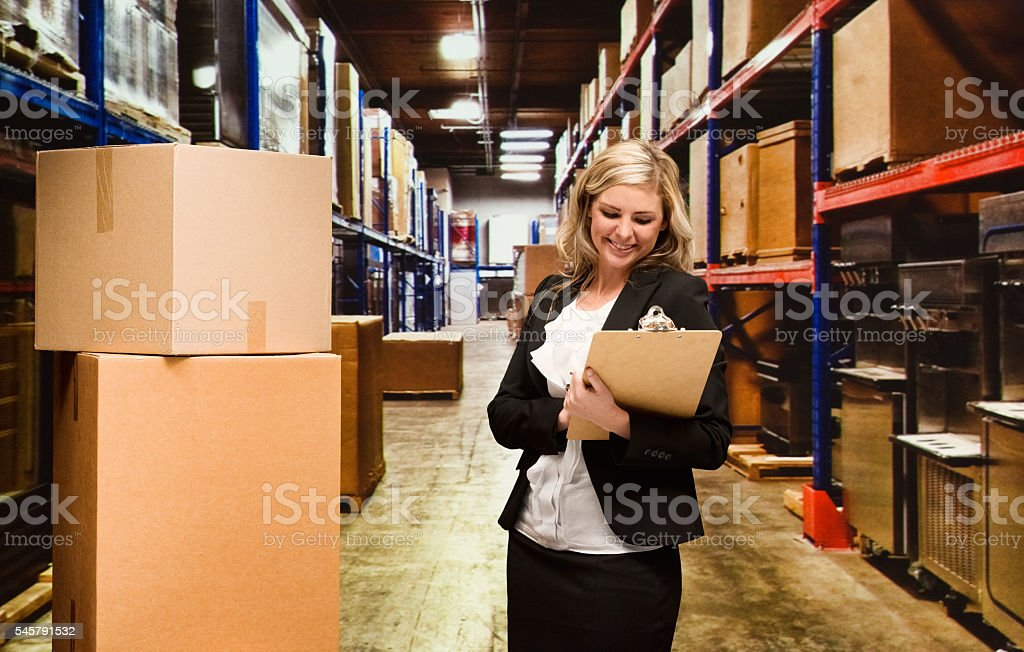 Smiling businesswoman working in warehouse stock photo