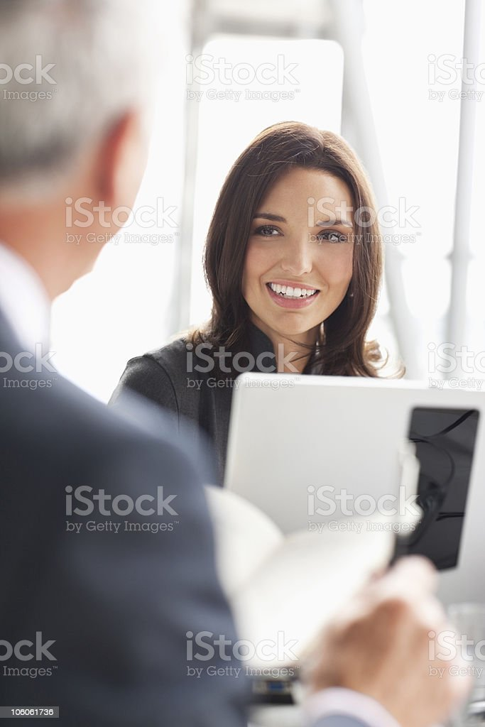 Smiling businesswoman working on laptop with businessman royalty-free stock photo