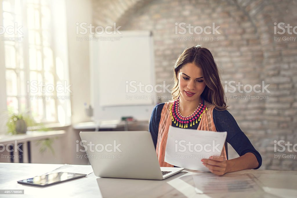 Smiling businesswoman working on paperwork and laptop in the office. stock photo