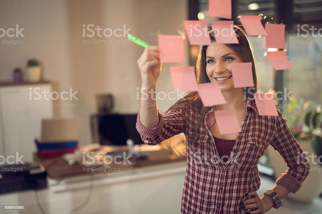 Smiling businesswoman writing adhesive notes on glass wall. stock photo
