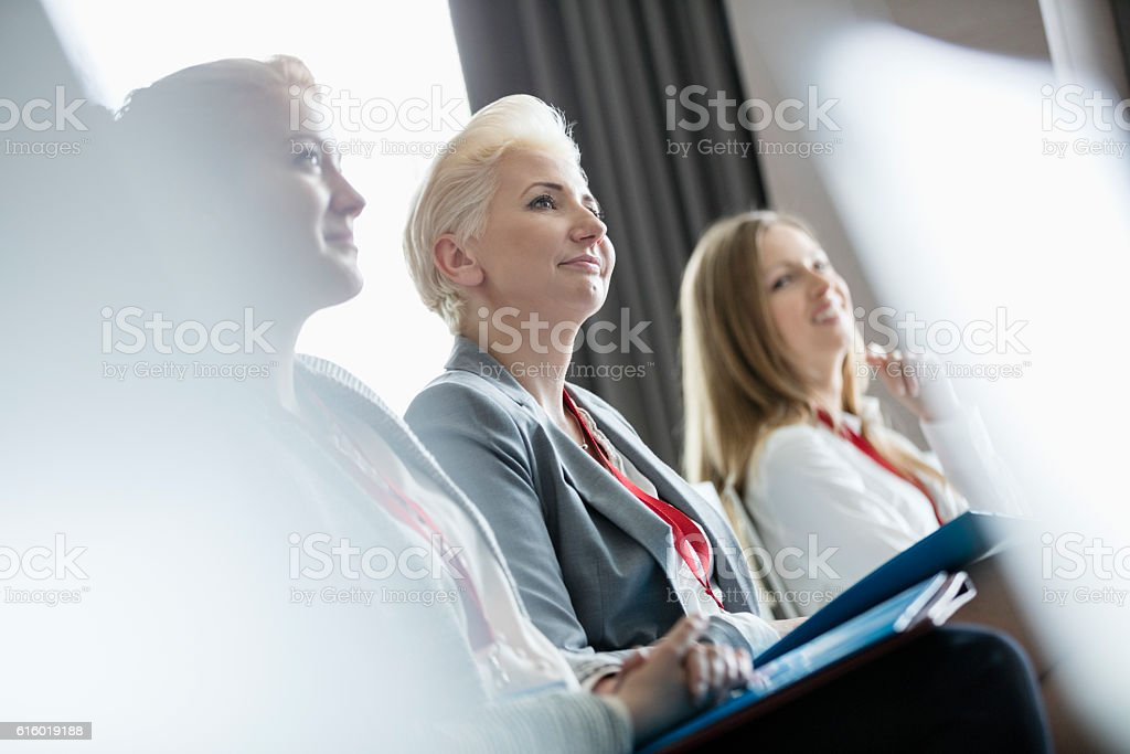 Smiling businesswomen attending seminar stock photo