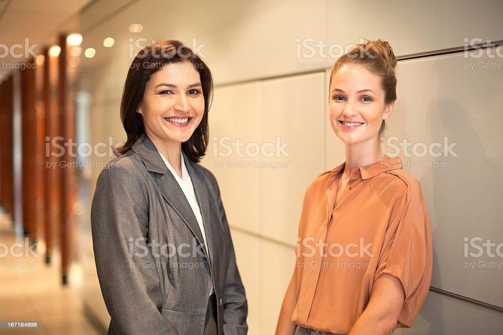 Smiling businesswomen in corridor royalty-free stock photo