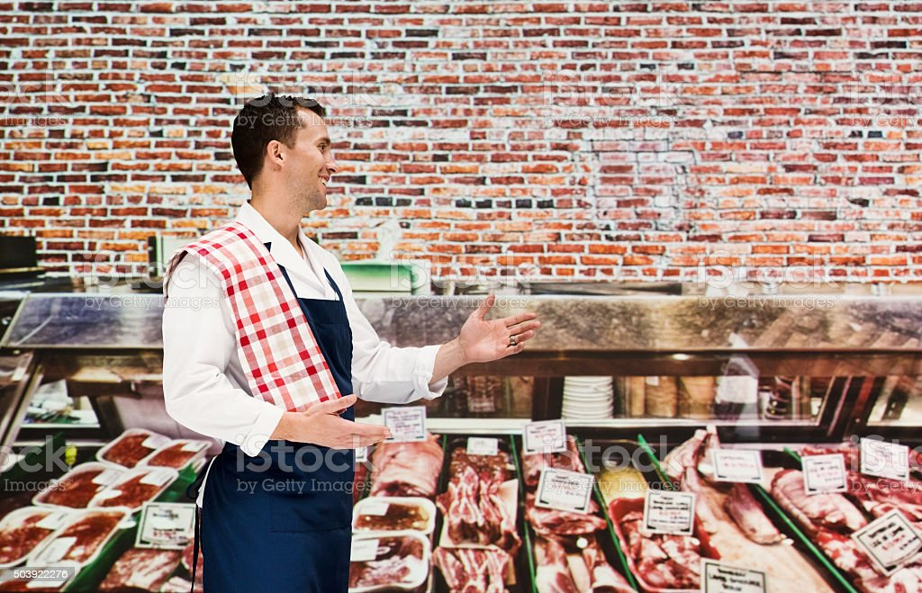 Smiling butcher in store and presenting stock photo
