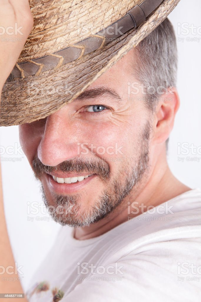 smiling cacasian man with a beard lifting a hat stock photo