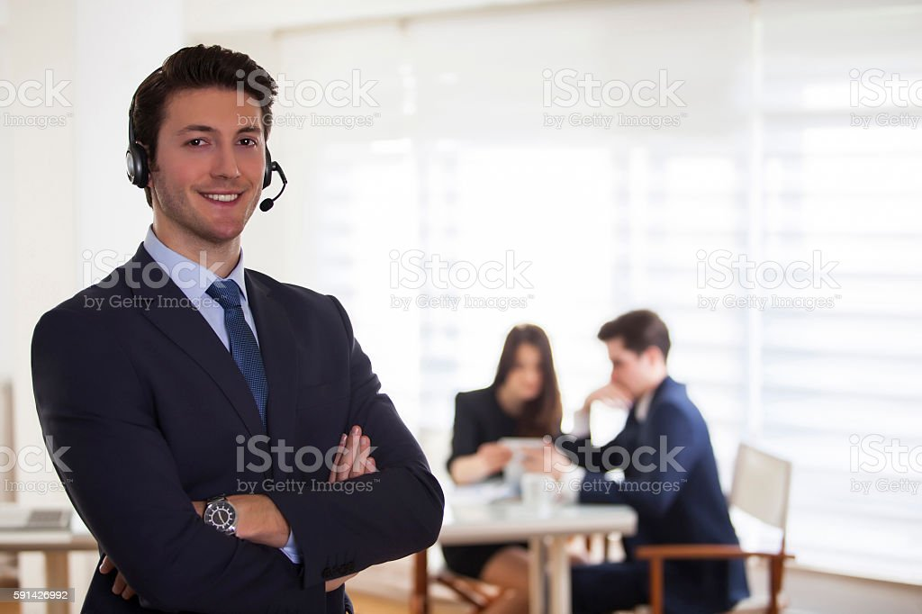 Smiling call center employee a telephone conversation in bright office stock photo