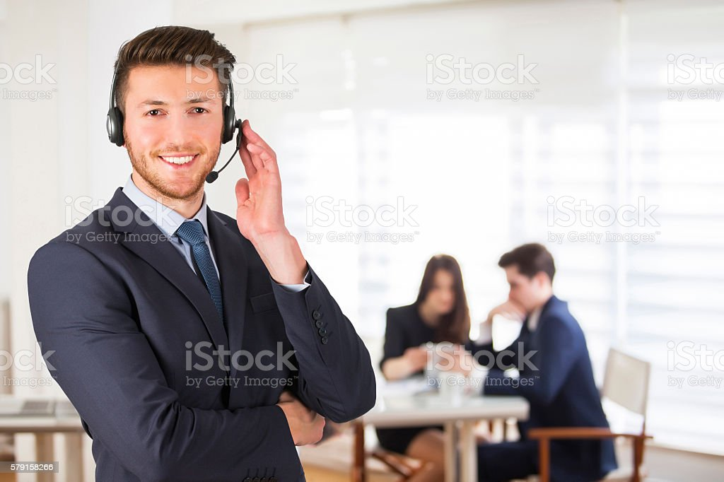 Smiling call center employee during a telephone conversation in office stock photo