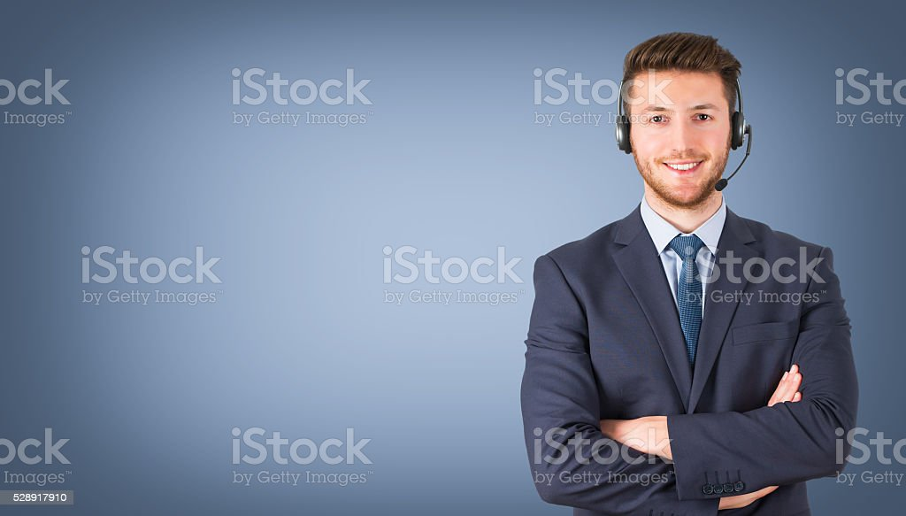 Smiling call center employee during a telephone conversation stock photo