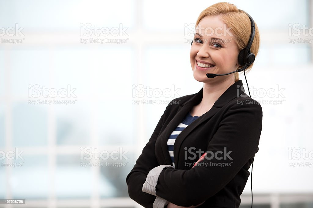 Smiling call center female operator with headphones stock photo