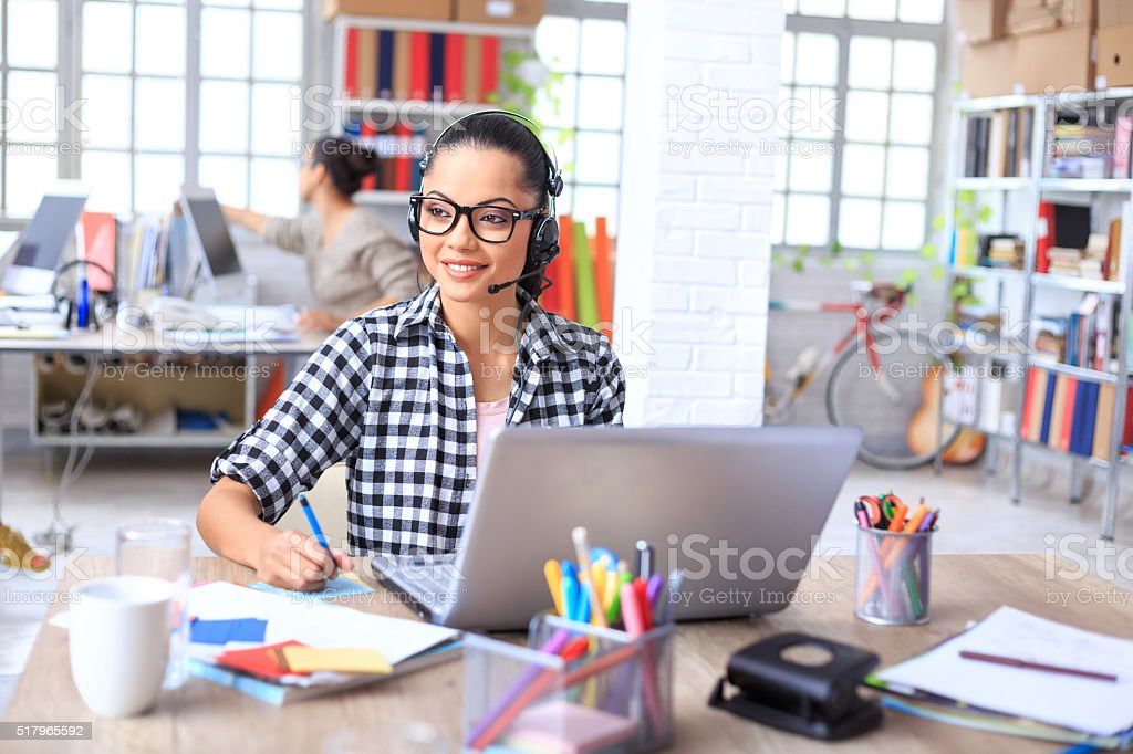 Smiling call center operator at work stock photo