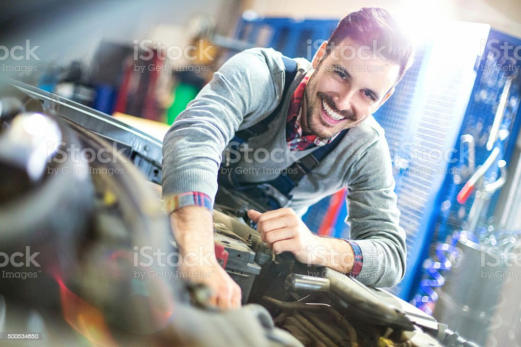 Smiling car mechanic dealing with an engine. stock photo