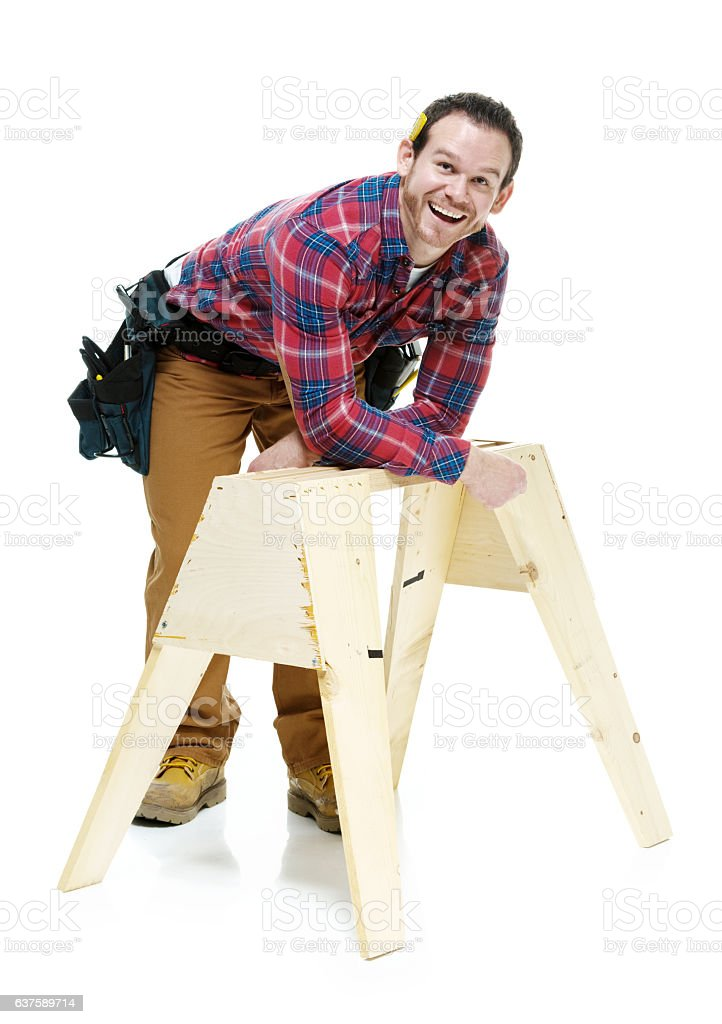 Smiling carpenter leaning on sawhorse stock photo