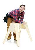 Smiling carpenter leaning on sawhorse