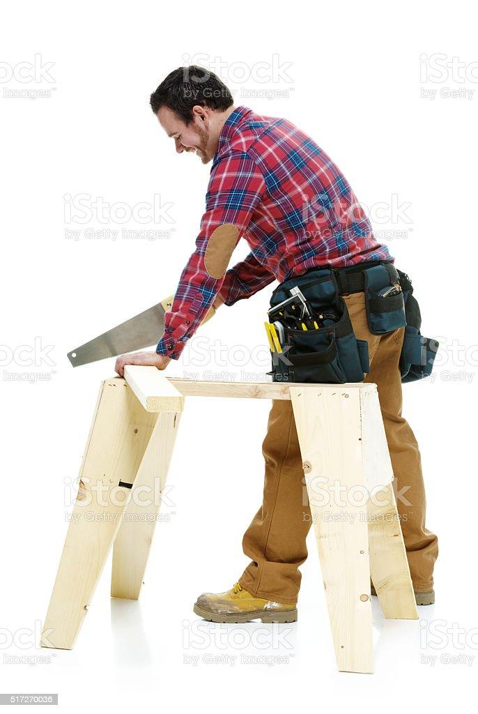 Smiling carpenter sawing stock photo