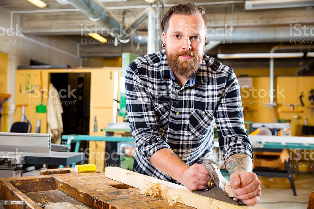 Smiling carpenter work with plane on wood plank in workshop stock photo