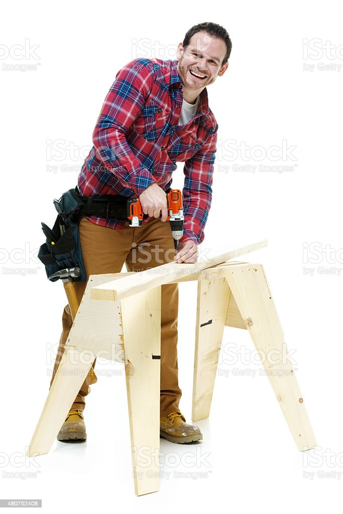 Smiling carpenter working with drill stock photo