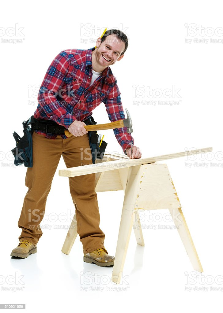 Smiling carpenter working with hammer stock photo