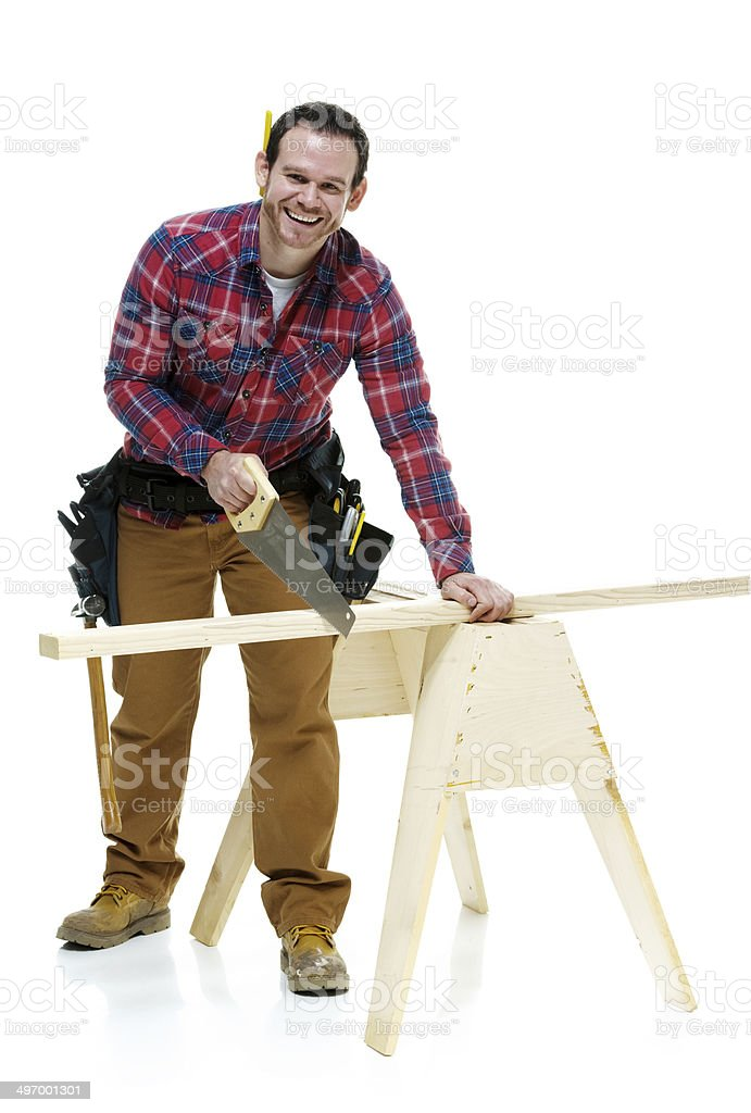 Smiling carpenter working with handsaw stock photo