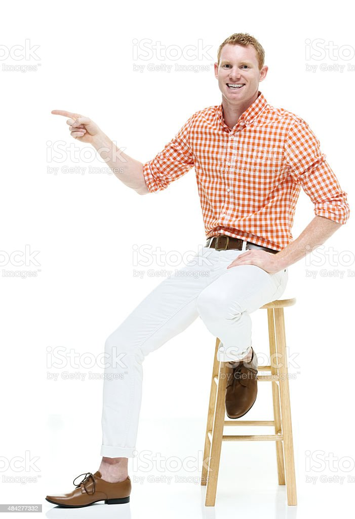 Smiling casual man on stool and pointing away stock photo
