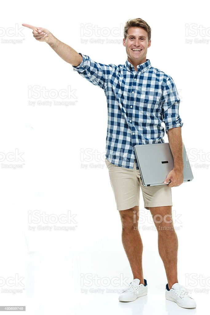 Smiling casual man pointing away stock photo