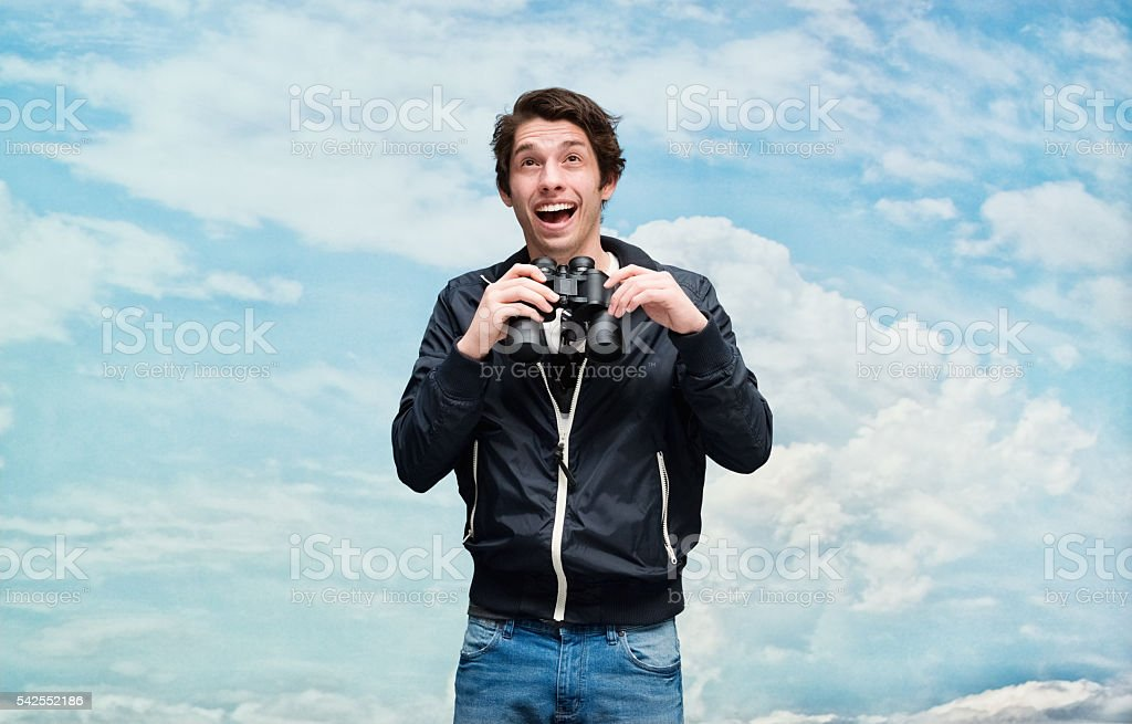 Smiling casual man searching with binoculars stock photo