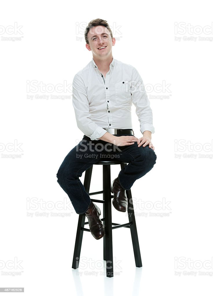 Smiling casual man sitting on stool stock photo