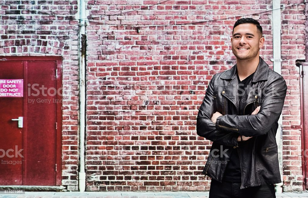 Smiling casual man standing in front of brick wall stock photo