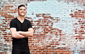 Smiling casual man standing in front of brick wall