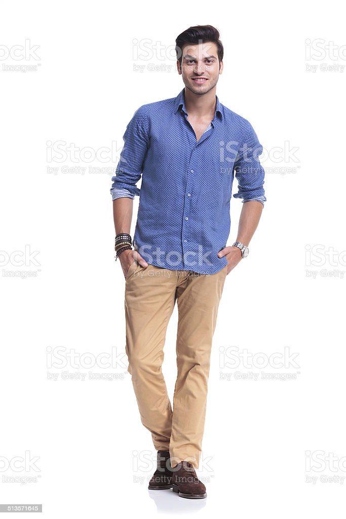 smiling  casual man standing with hands in  pockets stock photo