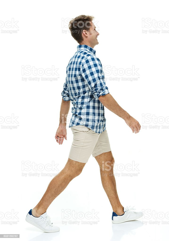 Smiling casual man walking and looking away stock photo