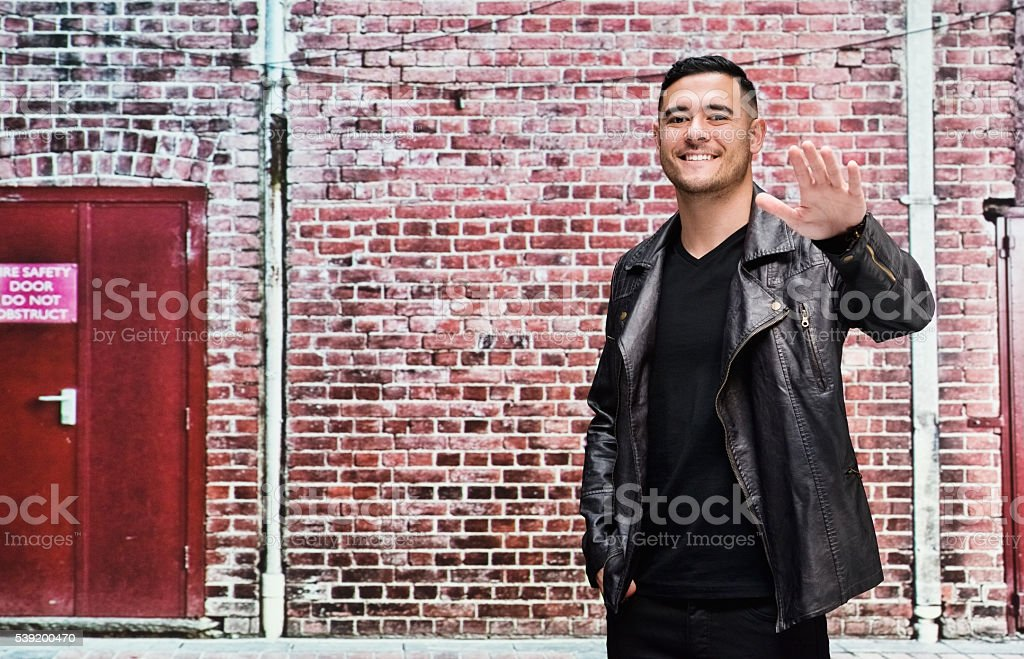 Smiling casual man waving hand stock photo