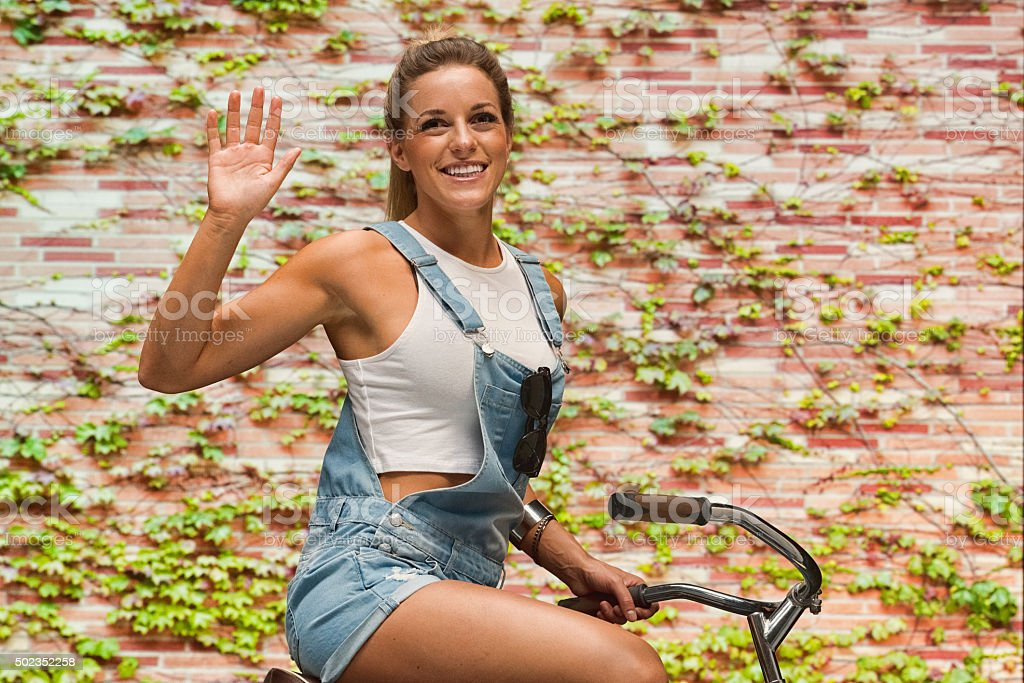 Smiling casual woman on bicycle and waving hand stock photo