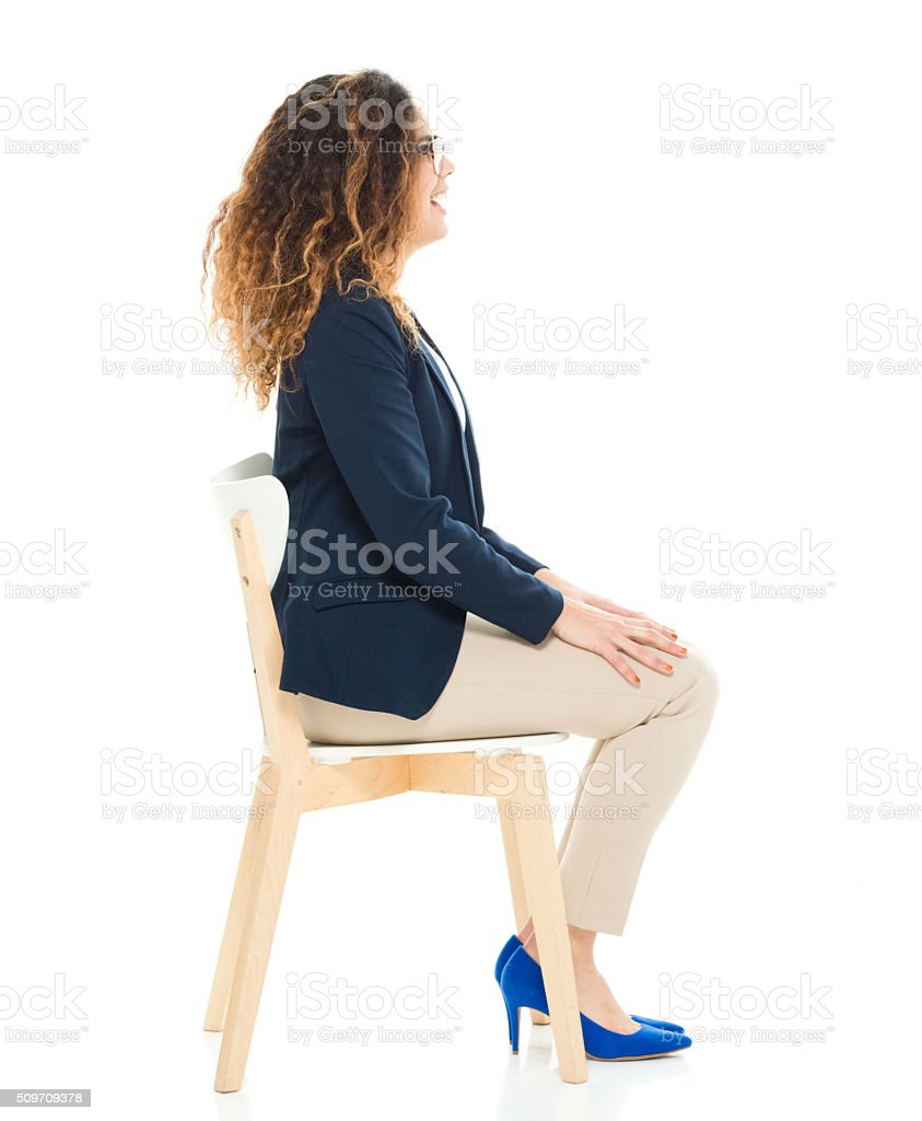 Smiling casual woman sitting on chair stock photo