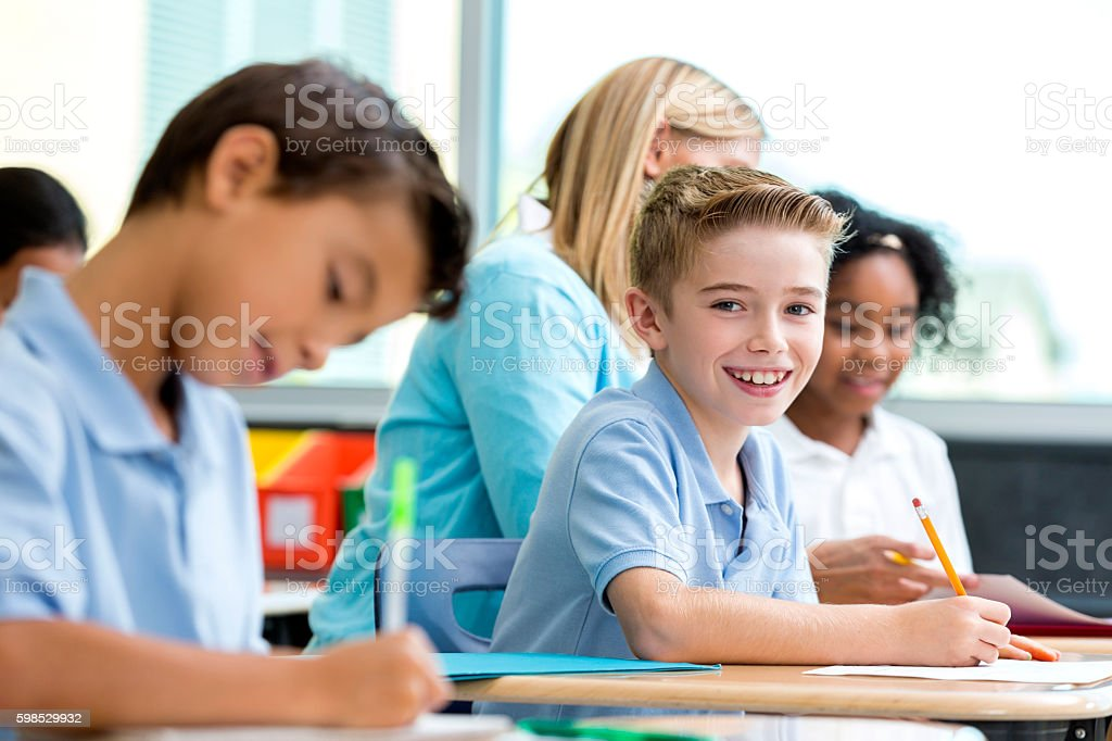 Smiling Caucasian boy sitting in classroom looking at camera stock photo