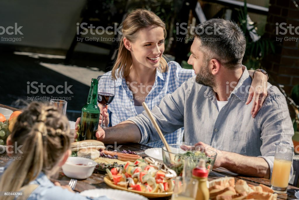 smiling caucasian couple with wine and beer spending time together on picnic stock photo