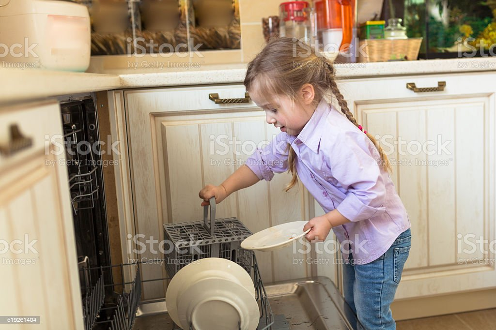 Smiling caucasian girl helping in  kitchen taking plates out of stock photo