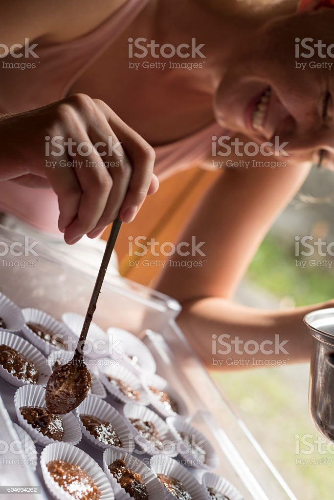 Smiling caucasian woman prepares chocolate pastries stock photo