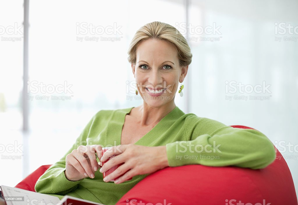 Smiling Caucasian woman sitting on a bean bag royalty-free stock photo