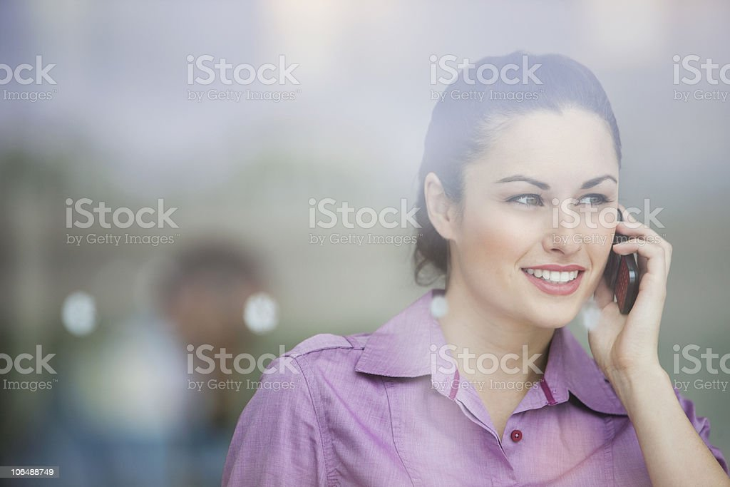 Smiling Caucasian woman talking on mobile phone standing behind glass window royalty-free stock photo
