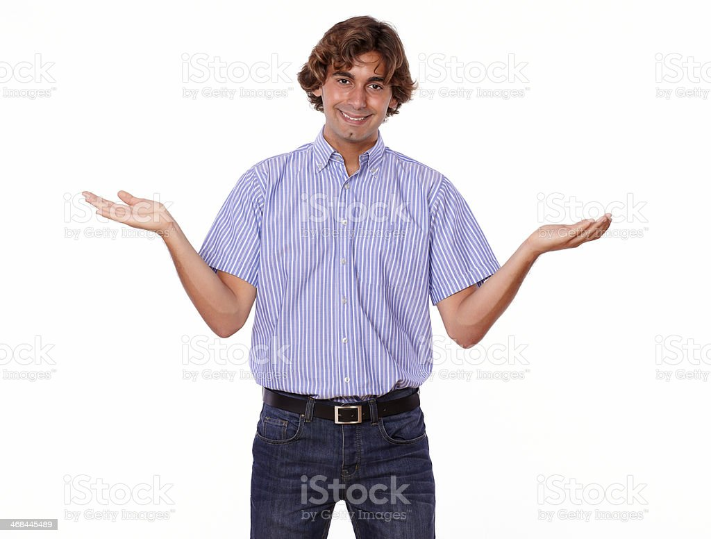 Smiling charismatic man in jeans holds palms out, royalty-free stock photo