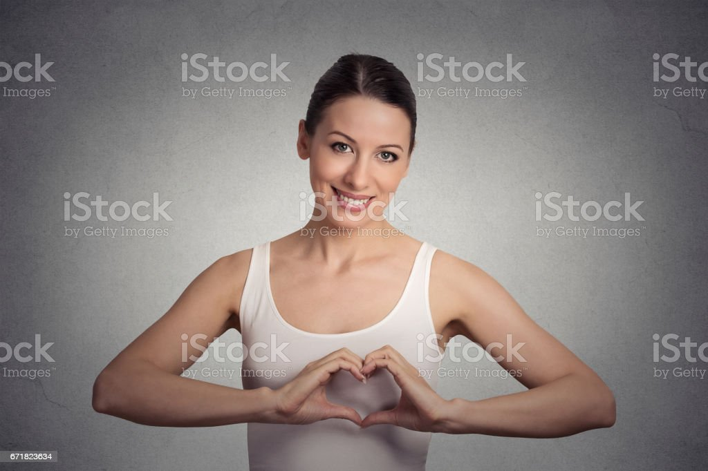 smiling cheerful happy young woman making heart sign with hands stock photo
