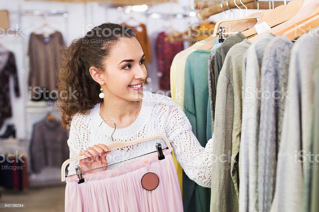 Smiling cheerful young woman shopping skirts stock photo