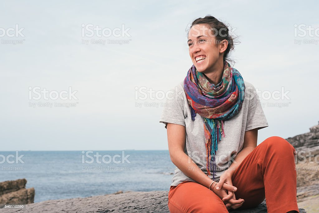 smiling cheerful young woman sitting on a sea rock stock photo