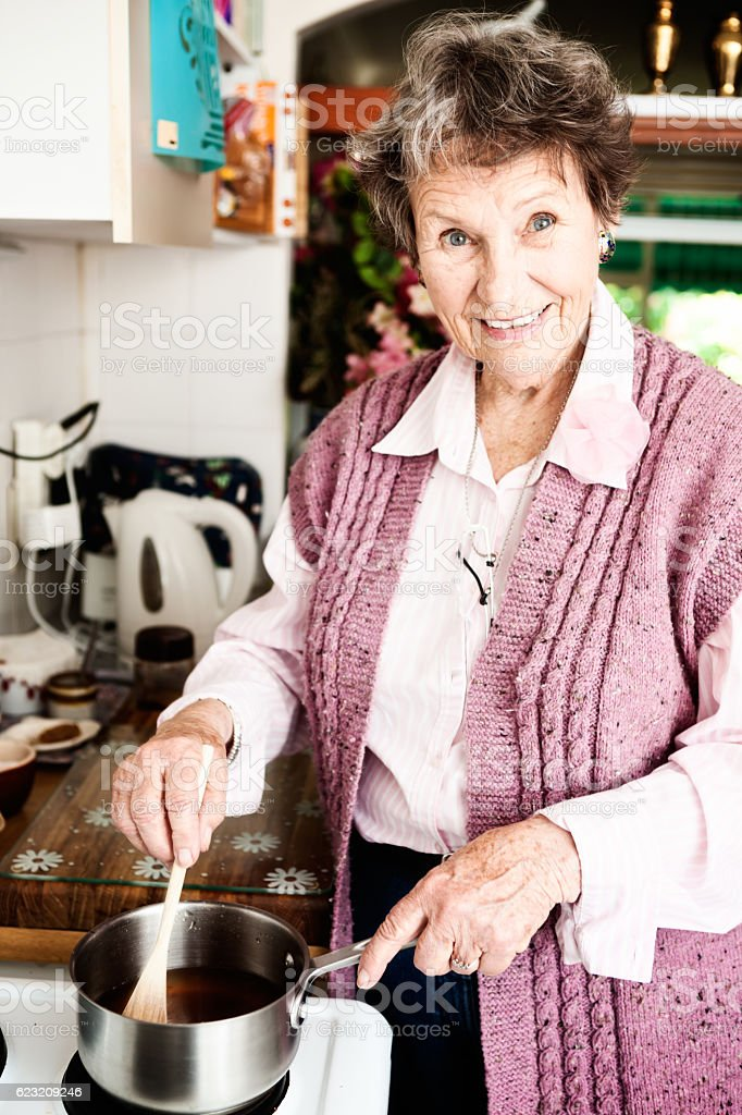 Smiling cheerfully, 80-plus woman cooks, still active and independent stock photo