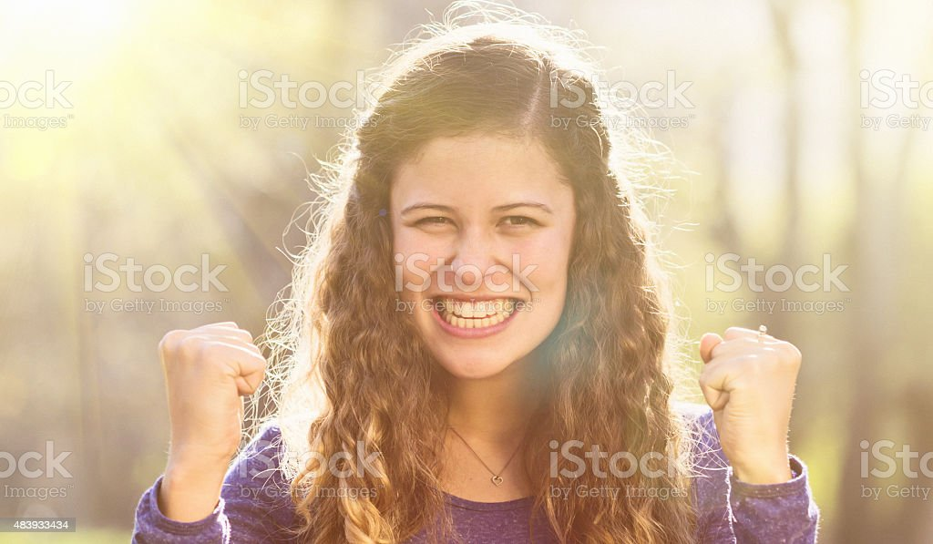 Smiling, cheering, triumphant beauty back lit by setting sun stock photo