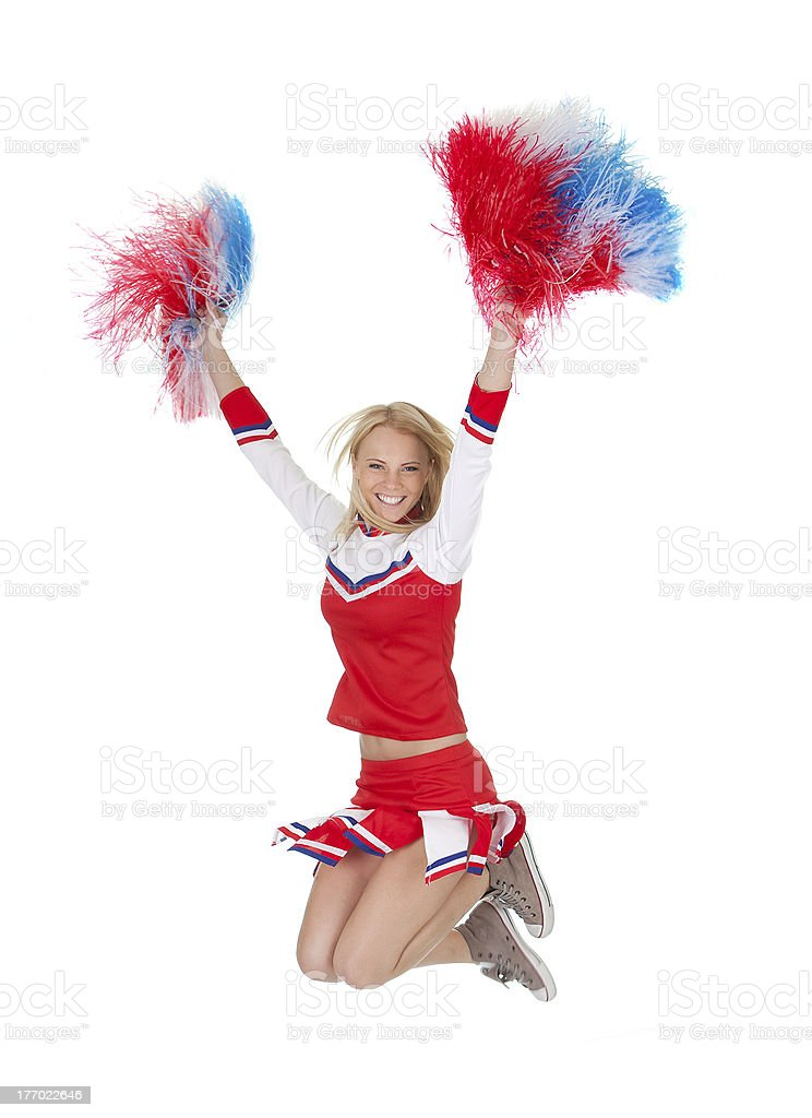 A smiling cheerleader jumping while holding Pom poms stock photo