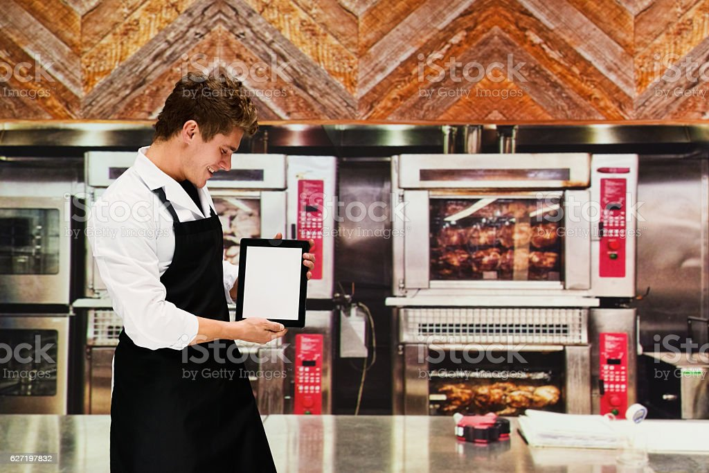 Smiling chef holding tablet in kitchen stock photo